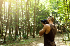 Bearded photographer man trekking among forest and taking pictures with dslr camera. Horizontal shape, copy space. Bearded photographer man trekking among forest Royalty Free Stock Photos