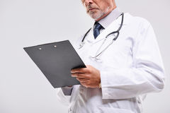 Bearded physician standing on a gray background stock photos