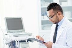 Bearded Physician Wrapped up in Work. Profile view of handsome young physician in eyeglasses filling in medical card while consulting patient at office, portrait Stock Photography