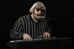 Bearded pianist singing at full throat. Bearded grey haired pianist singing at full throat on black background Stock Photography