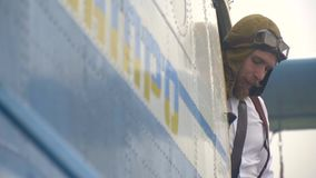 A bearded pilot in a vintage helmet looks out from Dnepropetrovsk aircraft, a bit slow motion stock video