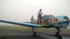 A bearded pilot in a vintage helmet stands on the wing of an airplane with a painted tiger stock video footage