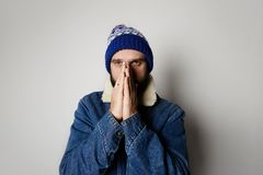 Bearded pensive man Wearing blue jeans and beanie on white background. Studio shot. Bearded positive handsome man Wearing blue jeans on white background. Studio royalty free stock image