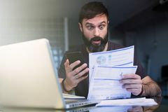 Bearded positive man working with laptop at home browsing documents . Businessman going through paperwork at home office. With unpaind bills royalty free stock image