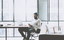Bearded product manager working on modern open space office. Stylish man texting message smartphone. Generic design. Notebook wood table. Horizontal mockup Royalty Free Stock Photo