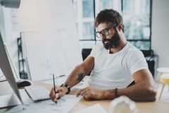 Bearded professional architect wearing eye glasses working at modern loft studio-office with desktop computer.Blurred Stock Image