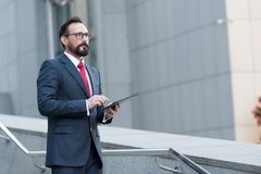 Bearded professional man broker standing outdoor while holding digital tablet in his hands. Modern businessman thinking overview. Bearded professional man broker Royalty Free Stock Photography