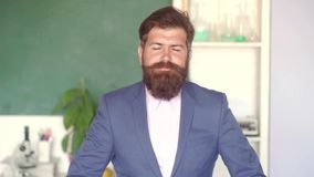 Bearded professor at school lesson at desks in classroom. School concept. Serious male Student studying in school. Young. Bearded teacher near chalkboard in stock video footage