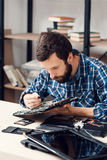 Bearded repairman disassemble computer motherboard Stock Photography