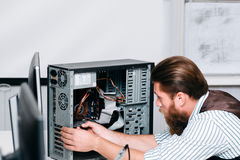 Bearded repairman disassembling computer unit royalty free stock images