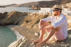 Bearded romantic male traveler in a hat and glasses meets the dawn on the shore of the bay stock photo