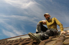 Bearded roofer resting on top of a roof sunny day Stock Photography