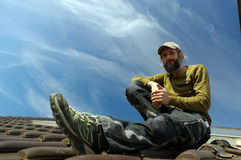 Bearded roofer resting on top of a roof sunny day Royalty Free Stock Photography