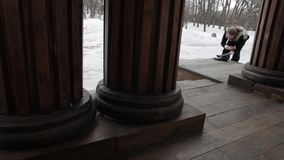 Bearded Russian costume in the 19th century, shines shoes on the porch of an old building stock footage