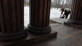 Bearded Russian in the 19ntury, shines shoes on the porch, wooden columns stock video