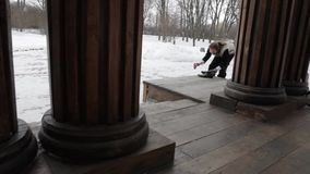 Bearded Russian in the 19ntury, shines shoes on the porch, wooden columns stock footage