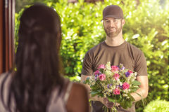 Bearded 20s man delivers flowers to young woman. Smiling bearded 20s men wearing brown cap and brown t-shirt delivers flowers to door of young brunette female royalty free stock images