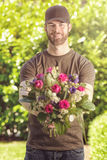 Bearded 20s man holding bunch of flowers Royalty Free Stock Images