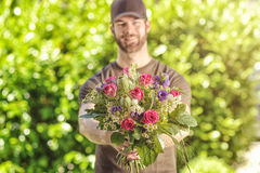 Bearded 20s man holding bunch of flowers Royalty Free Stock Photos