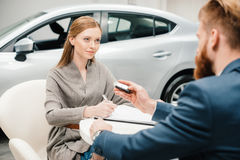 Bearded salesman giving new car key to young woman Royalty Free Stock Photos