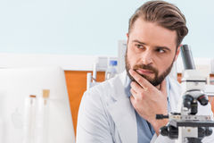 Bearded scientist working with microscope in laboratory. Pensive bearded scientist working with microscope in laboratory Royalty Free Stock Images