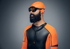 Bearded scuba diver male in orange neoprene suit isolated on gre Stock Photography