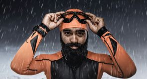 Bearded scuba diver under rain drops. Portrait of bearded scuba diver under rain drops over snow mountains background Stock Image