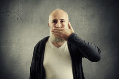 Bearded senior man covering his mouth Royalty Free Stock Image