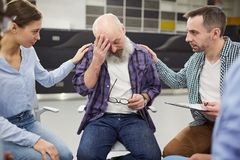 Bearded Senior Man Crying in Support Group. Portrait of senior men crying during group therapy session with two people comforting him, copy space stock images