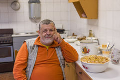 Bearded senior man sitting on a chair in kitchen Stock Photo