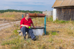 Bearded senior man sitting at country draw-well Royalty Free Stock Image