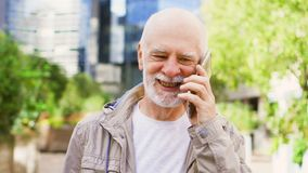 Senior man standing outdoors using smartphone. Downtown business dictrict on background. Bearded senior man standing outdoors using cellphone. Retired male stock footage
