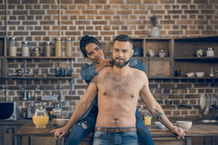 Bearded shirtless man and his girlfriend hugging in kitchen Stock Photos