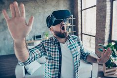Bearded, shocked, wondered man in shirt with open mouth in motio. N, getting experience wearing vr goggles headset, watching video, trying to touch something in Stock Photography