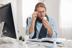 Bearded sick male office worker with spectacles on reads prescription of medicine. Young manager has bad cold, sits at. Table with pills, tablets, vitamins and Stock Photo