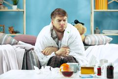 Bearded sick man with flue sitting on sofa at home. Illness, influenza, pain concept. Relaxation at Home. Healthcare stock image