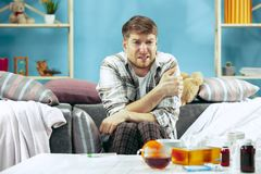 Bearded sick man with flue sitting on sofa at home. Illness, influenza, pain concept. Relaxation at Home. Healthcare royalty free stock photography