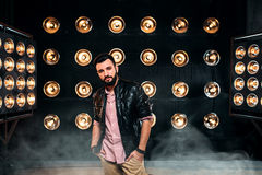 Bearded singer on stage with decorations of lights. Bearded singer in black leather jacket on the stage with the decorations of lights royalty free stock images