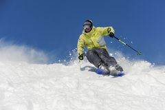 Bearded skier running down the mountain slope in resort of Gudauri, Georgia. Skier dressed in yellow and grey sportswear running down the mountain slope on the stock image
