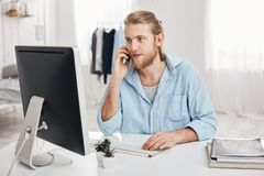 Bearded skilled young fair-haired businessman works on new project, sits in front of screen, has phone conversation. Discusses last financial report with Royalty Free Stock Photos