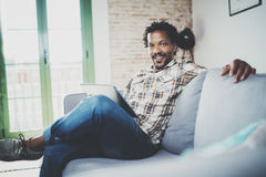 Bearded smiling American African man using tablet for video conversation while relaxing on sofa in modern home.Concept. Of young business people working at home Royalty Free Stock Photo