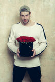 Bearded smiling man holds red rose box on textured wall. Bearded macho smiling man, brutal caucasian hipster with moustache in sweater and cap holds red rose Royalty Free Stock Photography