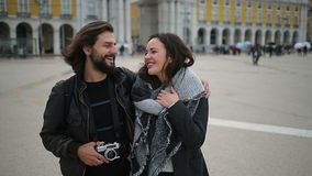 Bearded smiling man hugging girlfriend and pointing at distance. Cheerful tourists with photo camera walking on city square. Travel concept stock footage