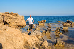 Bearded smiling man standing on the rocky coast Cape Greco Royalty Free Stock Photography