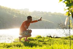 Bearded smiling man is training on the balance board. On a green meadow next to river on sunny evening. Back light Stock Image