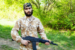 Bearded soldier with a rifle in the woods Royalty Free Stock Photography