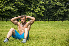 Bearded sportsman doing abs exercise in park Stock Photography
