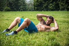 Bearded sportsman doing abs exercise in park Royalty Free Stock Photography