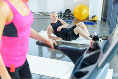 Bearded sportsman lying on mat and looking at woman exercising on treadmill Stock Photography