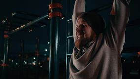 Close-up view of tensed face of young man training outdoors in night time. Bearded sportsman is tensing muscles during physical exercise in night time, detail stock footage